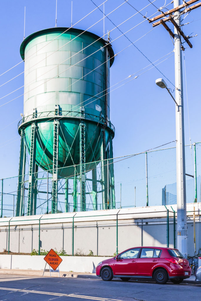 Vertical shot of a water tower behind a fence.