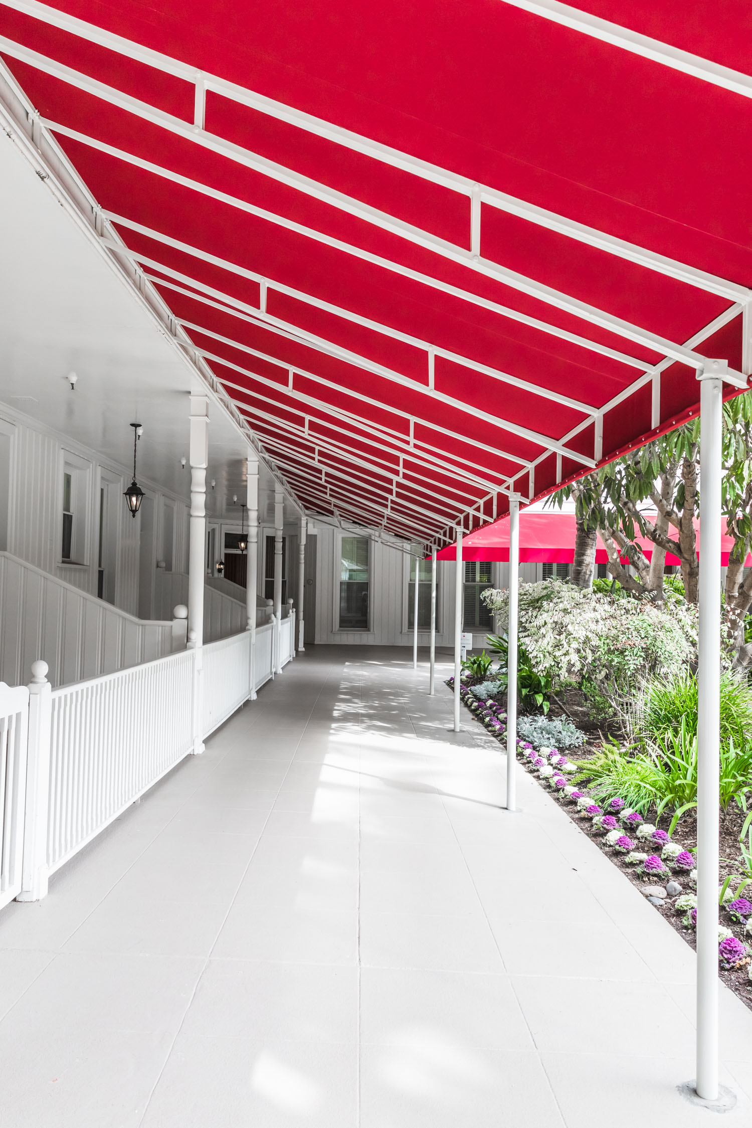 Vertical shot of a white outdoor hallway with a red overhang.