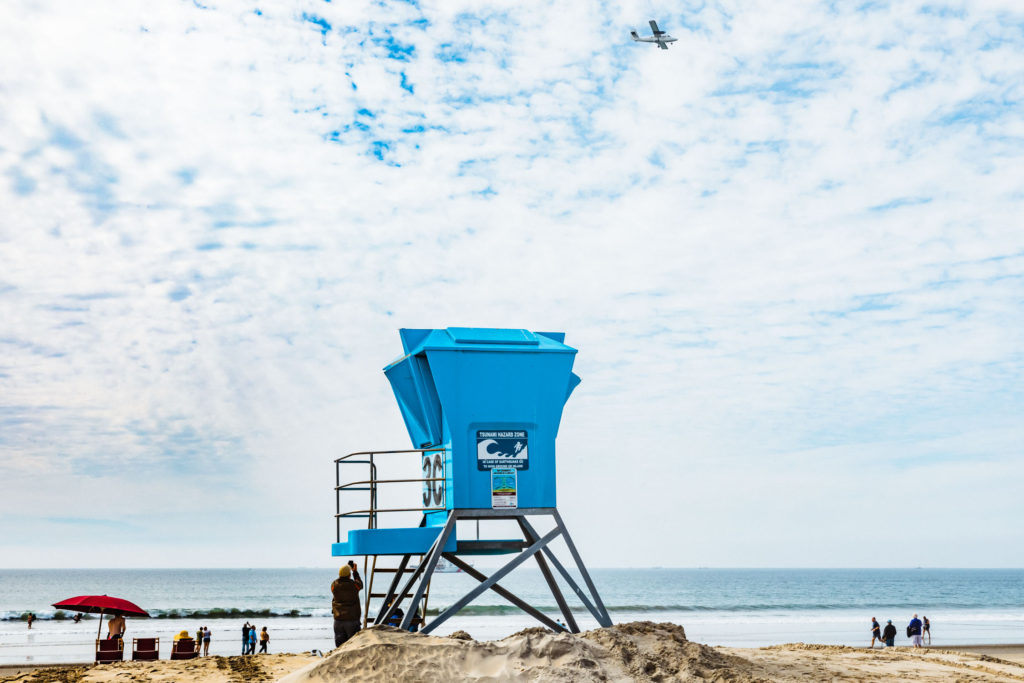 Horizontal shot of life guard tower on the beach with people looking up at a passing airplane.