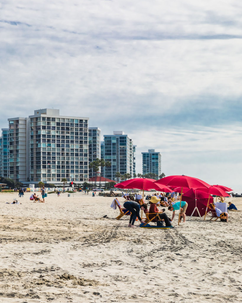 Vertical shot of people around red beach umbrellas with sky scrapper apartments in the background.